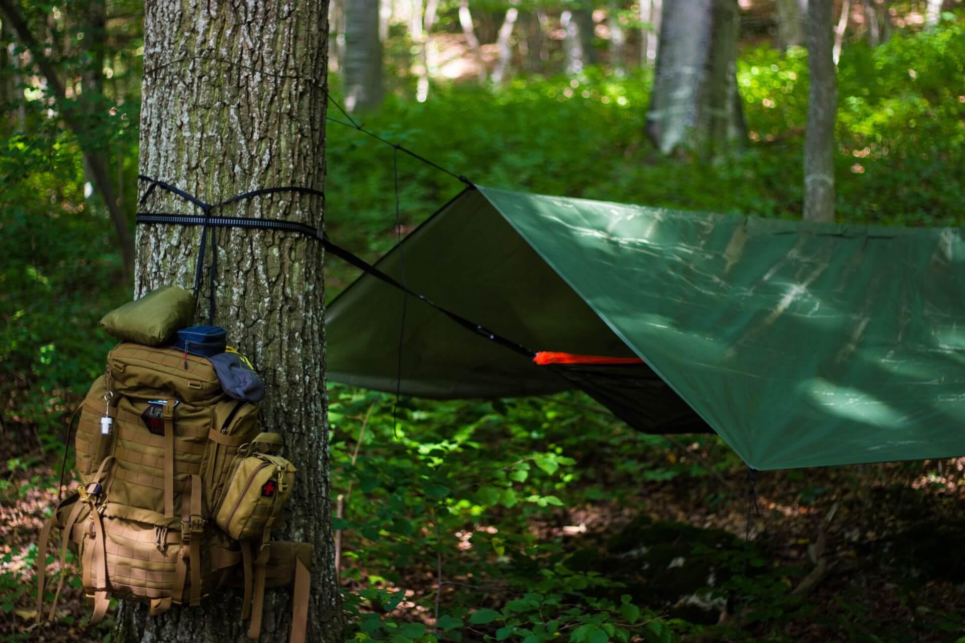 Symbolbild Mikroabenteur: Rucksack und gespannte Plane am Baum