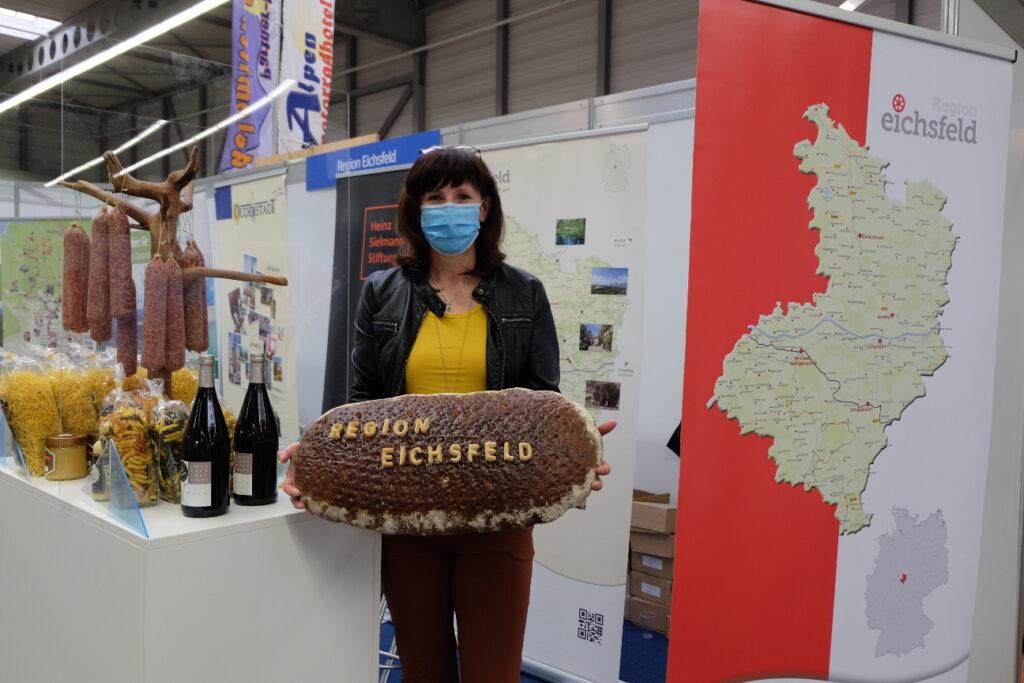 """Ausstellerin präsentiert ein Brot mit dem Schriftzug """"Region Eichsfeld"""""""
