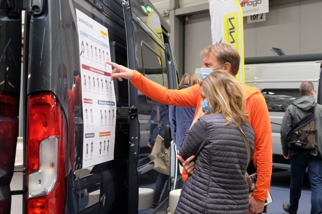 Besucher schauen sich einen Camper-Van und dessen Modell-Varianten an.
