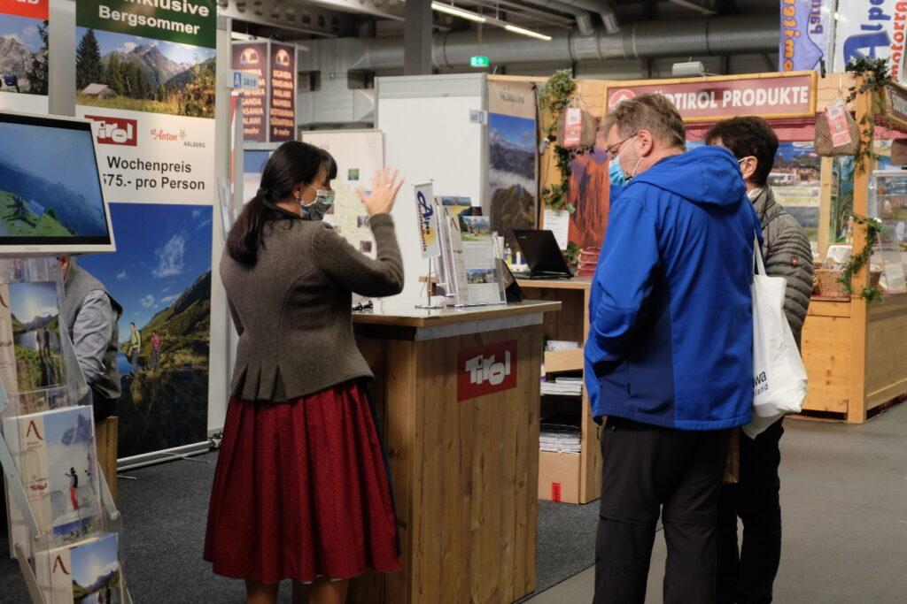 Beratung an einem Stand für Urlaub in den Alpen bei der Messe Reisen & Caravan